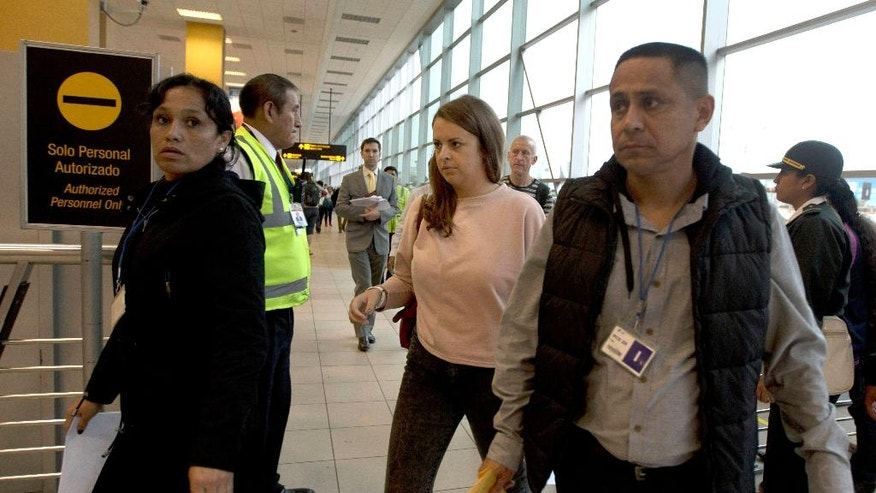 Melissa Reid, of Britain, center, walks before boarding a flight in Lima, Peru, Tuesday, June 21, 2016. Reid was deported from Peru, along with Irish-born Michaella McCollum, after being detained on Aug. 6, 2013, at Lima's airport for allegedly trying to smuggle cocaine on a flight to Spain. (AP Photo/Martin Mejia)