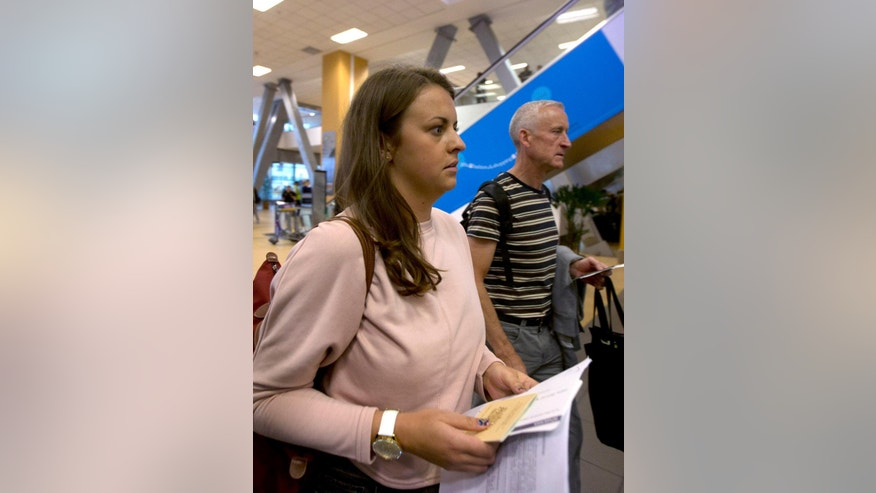 Melissa Reid, of Britain, walks next to her father William Reid, before boarding a flight in Lima, Peru, Tuesday, June 21, 2016. Reid was deported from Peru, along with Irish-born Michaella McCollum, after being detained on Aug. 6, 2013, at Lima's airport for allegedly trying to smuggle cocaine on a flight to Spain. (AP Photo/Martin Mejia)