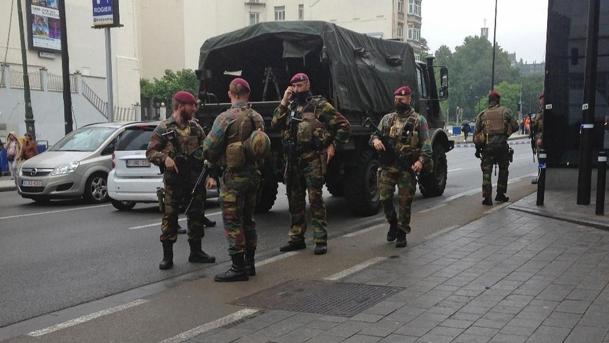 Belgian soldiers gather near a blocked off area in downtown Brussels Tuesday June 21, 2016 after Belgian authorities took a man into custody following a pre-dawn security alert at a major shopping center. The security operation followed an alert about a suspicious package. (AP Photo/Virginia Mayo)