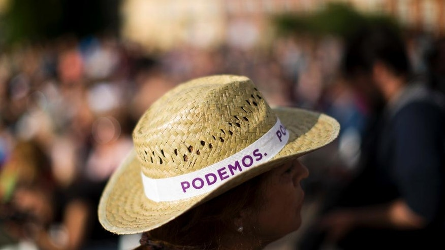 In this Friday, June 17, 2016 photo, a volunteer of Spain's Podemos party stands during a campaign rally in Madrid. Just six months after casting ballots for a new government, Spaniards are heading back to the polls in an unprecedented repeat election. (AP Photo/Francisco Seco)