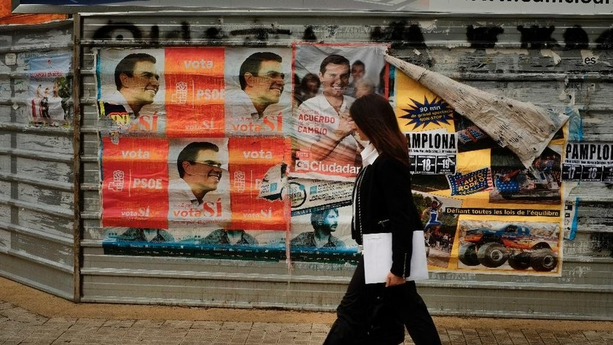 In this Thursday June 16, 2016 photo, a woman walks past electoral campaign posters, in Pamplona, northern Spain. Just six months after casting ballots for a new government, Spaniards are heading back to the polls in an unprecedented repeat election. (AP Photo/Alvaro Barrientos)