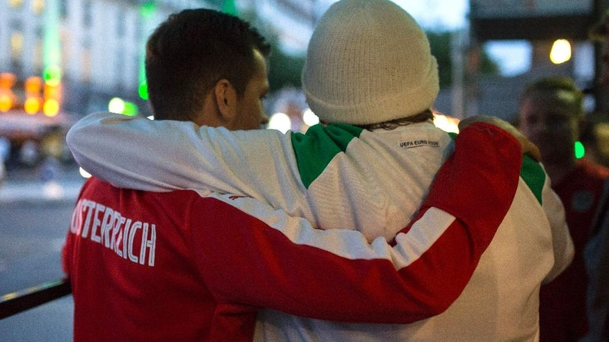 An Austrian fan, left, and a Northern Ireland fan hug in Paris, France, Monday, June 20, 2016. While fans from other countries have damaged their reputations amid ugly scenes at Euro 2016, Irish supporters have enhanced theirs with their antics amid shows of camaraderie, goodwill and kindness. (AP Photo/Kamil Zihnioglu)