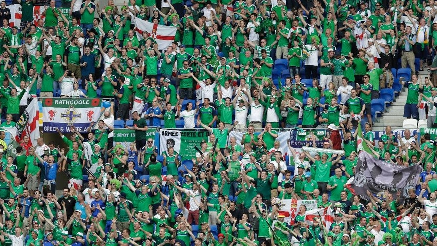 FILE - In this Thursday, June 16, 2016 file photo, Northern Ireland fans cheer on the stands during the Euro 2016 Group C soccer match between Ukraine and Northern Ireland at the Grand Stade in Decines-Charpieu, near Lyon, France. While fans from other countries have damaged their reputations amid ugly scenes at Euro 2016, Irish supporters have enhanced theirs with their antics amid shows of camaraderie, goodwill and kindness. (AP Photo/Pavel Golovkin, File)