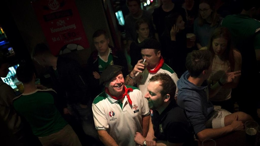 A Northern Ireland fan, left, talks to a Wales soccer fan in a pub in Paris, France, Monday, June 20, 2016. While fans from other countries have damaged their reputations amid ugly scenes at Euro 2016, Irish supporters have enhanced theirs with their antics amid shows of camaraderie, goodwill and kindness. (AP Photo/Kamil Zihnioglu)