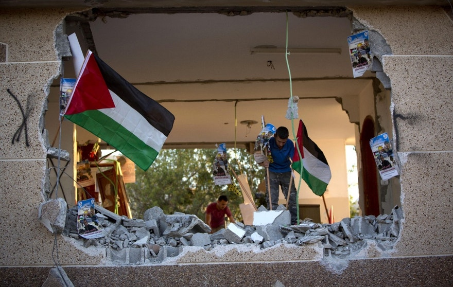 Palestinians place national flags and party banners in the house of Bashar Masalha?? after it was demolished by the Israeli army in the village of Hajja, near the West Bank city of Nablus, Tuesday, June 21, 2016. On Tuesday troops demolished the home of Masalha who stabbed to death an American tourist and war veteran in an attack earlier this year. Israel says it carries out housing demolitions to deter future attacks. The Palestinians consider it a form of collective punishment. (AP Photo/Majdi Mohammed