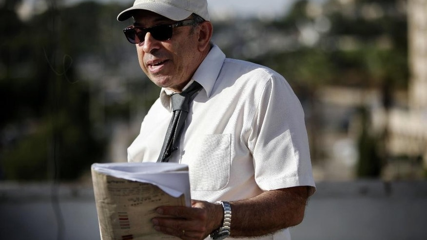 In this May 17, 2016 photo, Israeli lawyer Stephen Berman inspects a construction site on land owned by Palestinian Mohammad Abu Ta'a, in east Jerusalem. Abu Ta'a discovered some years ago that the Israeli government had expropriated the piece of land in Jerusalem belonging to his family and handed it over to a leading organization that oversees Jewish settlement building in the West Bank. Now, the Palestinian landowner is fighting back in an unusual way -- enlisting Berman whose inside knowledge of the system is helping Abu Ta'a expose the settler organization's property grab. (AP Photo/Mahmoud Illean)