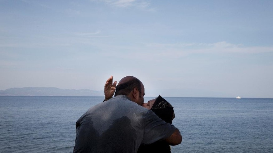 FILE - In this Wednesday, Sept. 9, 2015 file photo, a woman and a man kiss as they arrive with others migrants from Turkey to Lesbos island, Greece, on a dinghy. In a year when more than a million people arrived on European shores, the U.N. refugee agency said Monday, June 20, 2016 that continued conflicts and persecution in places like Syria and Afghanistan fueled a nearly 10-percent increase in the total number of refugees and internally displaced people in 2015. (AP Photo/Petros Giannakouris, File)