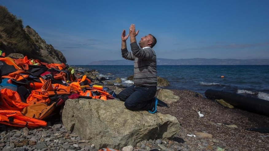FILE - In this Oct. 1, 2015 file photo, a refugee prays shortly after he and other migrants arrived on a dinghy from the Turkish coast to the northeastern Greek island of Lesbos. In a year when more than a million people arrived on European shores, the U.N. refugee agency said Monday, June 20, 2016 that continued conflicts and persecution in places like Syria and Afghanistan fueled a nearly 10-percent increase in the total number of refugees and internally displaced people in 2015.(AP Photo/Santi Palacios, File)