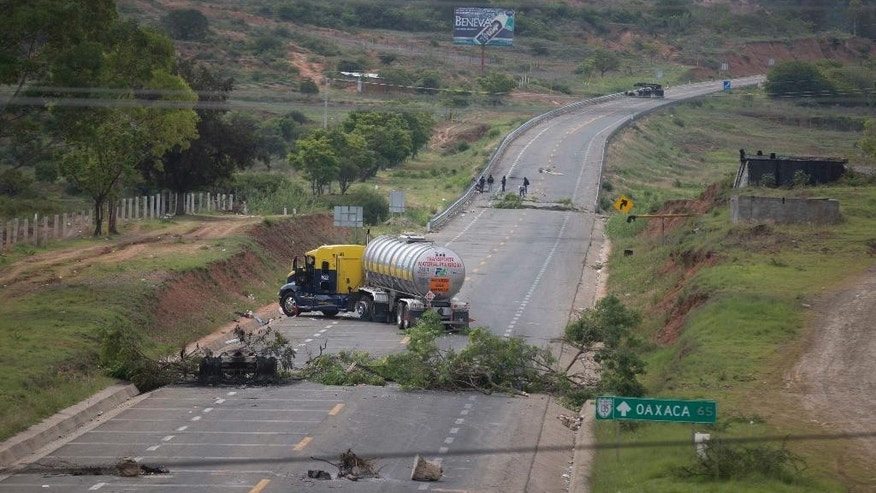 Trucks block the highway in Oaxaca state, near the town of Nochixtlan, Mexico, Monday, June 20, 2016. Mexican police say few teachers were involved in violence at a weekend highway protest in which six people died. The teachers are protesting against plans to overhaul the country's education system which include federally mandated teacher evaluations. (AP Photo/Eduardo Verdugo)