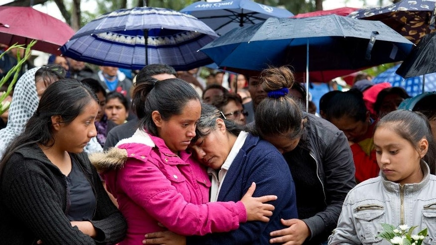 The mother of Jesus Cadena, who died last Sunday during the clearing of the highway by police, is comforted by relatives, in Nochixtlan, in Oaxaca state, Mexico, Tuesday, June 21, 2016. Violence erupted during the weekend in which at least six people died in confrontations between the police and striking teachers. The teachers are protesting against plans to overhaul the country's education system which include federally mandated teacher evaluations. (AP Photo/Eduardo Verdugo)