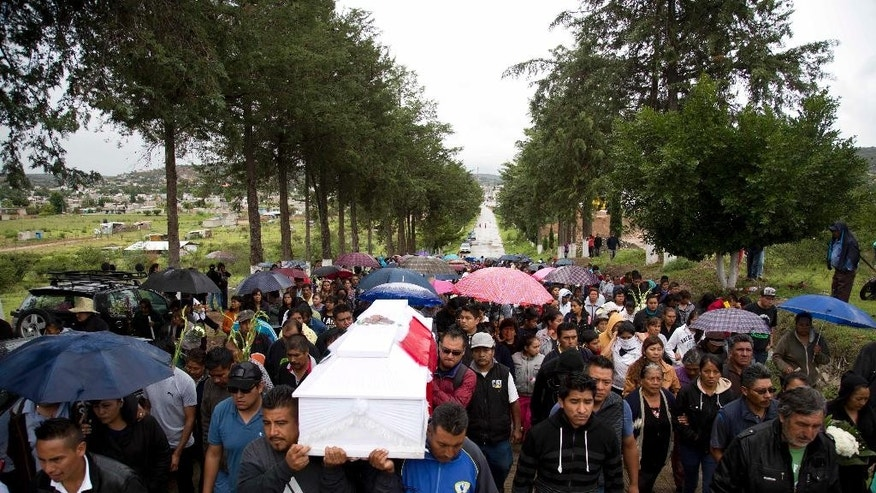 People carry the coffin of Jesus Cadena, who died last Sunday during the clearing of the highway by police, in Nochixtlan, in Oaxaca state, Mexico, Tuesday, June 21, 2016. Violence erupted during the weekend in which at least six people died in confrontations between the police and striking teachers. The teachers are protesting against plans to overhaul the country's education system which include federally mandated teacher evaluations. (AP Photo/Eduardo Verdugo)
