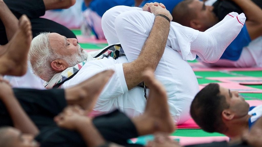 Indian Prime Minister Narendra Modi performs yoga along with thousands of Indians in Chandigarh, India, Tuesday, June 21, 2016. Millions of yoga enthusiasts are bending their bodies in complex postures across India as they take part in a mass yoga program to mark the second International Yoga Day. (AP Photo/Saurabh Das)