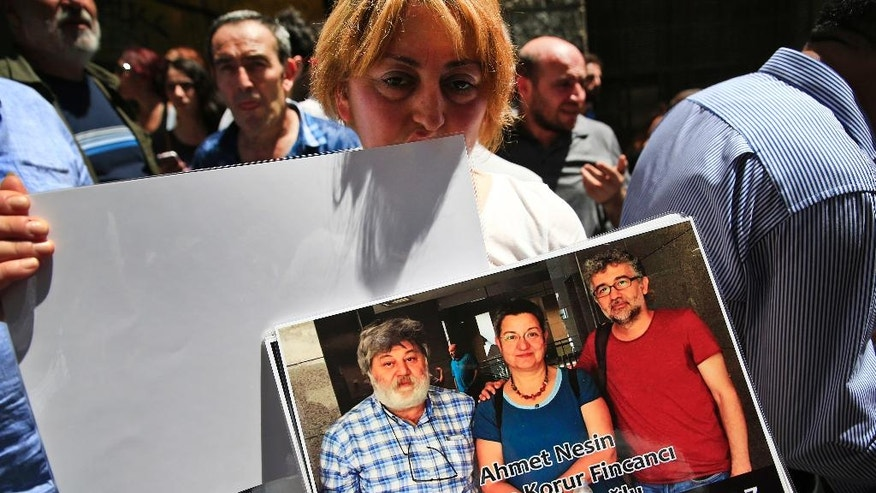 """A protester holding a photograph of from left to right, journalist Ahmet Nesin, academic Sebnem Korur Fincanci and Reporters Without Borders' local representative Erol Onderoglu, demonstrates against their jailing outside the offices of Ozgur Gundem, a pro-Kurdish publication, in Istanbul, Tuesday, June 21, 2016. The three, along with others had participated in a solidarity campaign in support of the paper, already subject to multiple investigations and lawsuits, were placed in pretrial arrest by a Turkish court Monday over charges of disseminating """"terrorist propaganda"""".  (AP Photo/Lefteris Pitarakis)"""