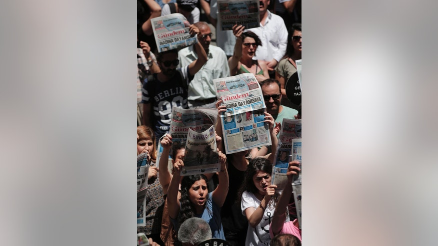 """Protesters demonstrate against the jailing of two journalists and an academic, outside the offices of Ozgur Gundem, a pro-Kurdish publication, in Istanbul, Tuesday, June 21, 2016. Reporters Without Borders' local representative Erol Onderoglu, along with journalist Ahmet Nesin and academic Sebnem Korur Fincanci, who had participated in a solidarity campaign in support of the paper, already subject to multiple investigations and lawsuits, were placed in pretrial arrest by a Turkish court Monday over charges of disseminating """"terrorist propaganda"""". (AP Photo/Lefteris Pitarakis)"""