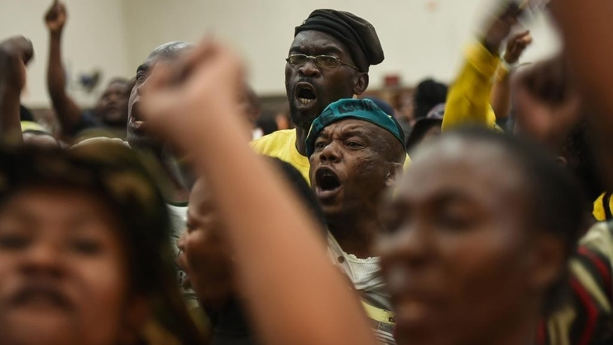Angry residents shout after refusing to accept the replacement of Pretoria's mayoral candidate at a community center in Atteridgeville, Pretoria, South Africa, Tuesday, June 21, 2016. Some residents in several poor areas of South Africa's capital, Pretoria, blocked roads, looted shops and burned vehicles Tuesday in riots attributed to discontent over the selection of the ruling party's mayoral candidate. (AP Photo/Shiraaz Mohamed)