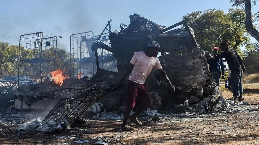 A man carries steel from a burnt truck on a road in Atteridgeville, Pretoria, South Africa, Tuesday, June 21, 2016. Some residents in several poor areas of South Africa's capital, Pretoria, blocked roads, looted shops and burned vehicles Tuesday in riots attributed to discontent over the selection of the ruling party's mayoral candidate. (AP Photo/Shiraaz Mohamed)