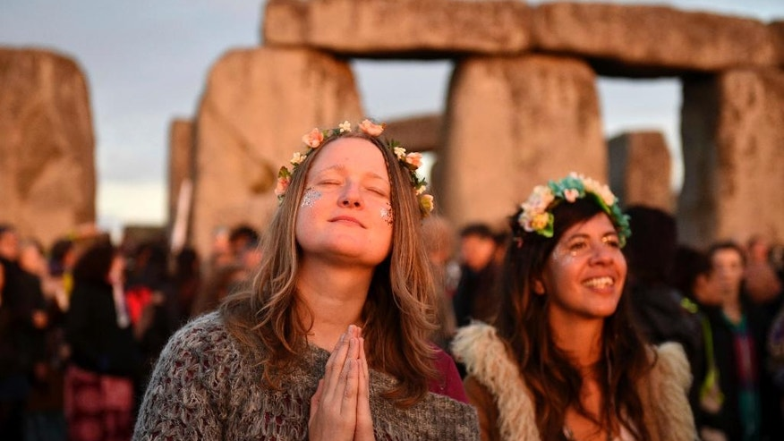 People gather to see the new dawn at the ancient stone circle Stonehenge, during the Summer Solstice, the longest day of the year, in Wiltshire Tuesday June 21, 2016.  (Andrew Matthews/PA via AP) UNITED KINGDOM OUT, NO SALES, NO ARCHIVES