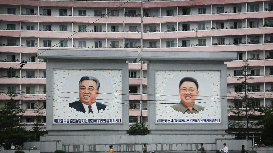North Koreans are dwarfed against giant portraits of the late North Korean leaders Kim Il Sung and Kim Jong Il as they walk past an apartment building on Wednesday, June 22, 2016, in Wonsan, North Korea. (AP Photo/Wong Maye-E)