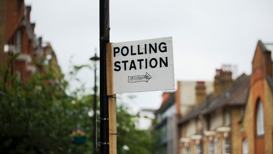 A sign points towards a referendum polling station in London, Wednesday, June 22, 2016. Britain votes whether to stay in the European Union in a referendum on Thursday. (AP Photo/Matt Dunham)