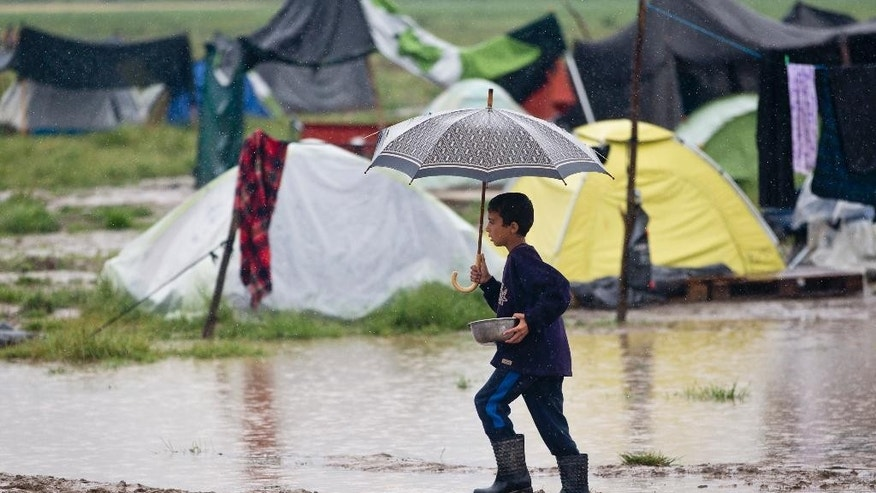 FILE - In this May 21, 2016 file photo, a boy carries a dish through a flooded part of the migrant camp in Idomeni, Greece. The medical aid organization Doctors Without Borders announced Friday, June 17, 2016 that it will no longer seek European Union funding in protest against the EU's much-maligned migrant deal with Turkey. (AP Photo/Darko Bandic, File)