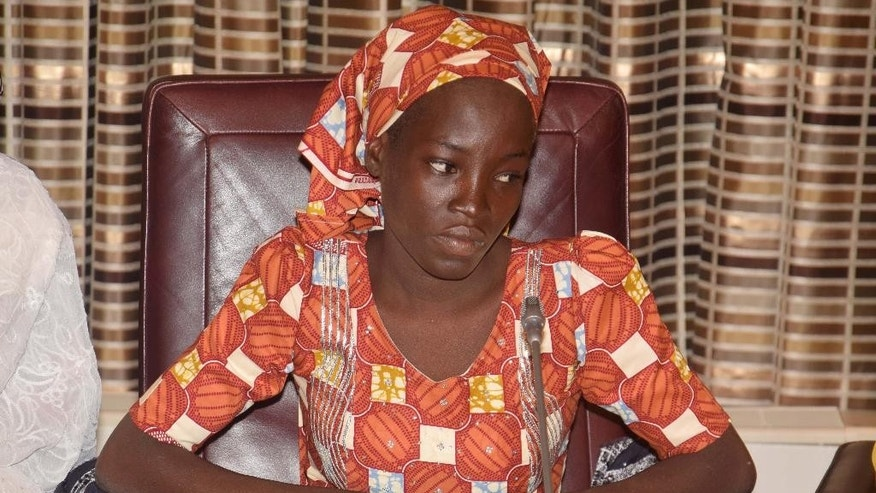 FILE- In this Thursday, May. 19, 2016 file photo, Amina Ali, the rescue Chibok school girl, sits during a meeting with Nigeria's President Muhammadu Buhari at the Presidential palace in Abuja, Nigeria. Nigeria's Bring Back Our Girls movement demanded Wednesday, June. 22, 2016 that the government provide news of the only one of 219 kidnapped schoolgirls to escape the clutches of the Boko Haram extremist group. (AP Photo/Azeez Akunleyan, File)