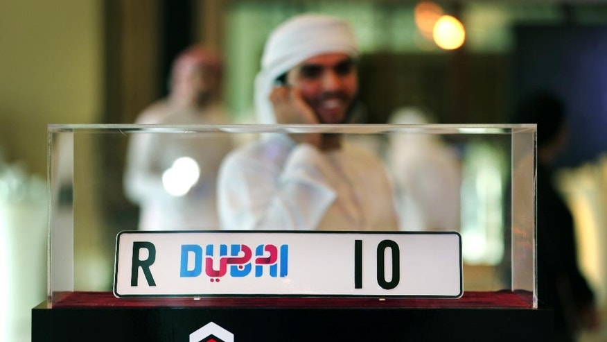 "In this Tuesday, June 21, 2016 photo, an Emirati man talks on his mobile phone next to the ""R Dubai 10"" license plate in its glass case, which was one of many items displayed in the Emirates Auction to be sold for AED 9.7 million ($ 2.65 million) in Dubai, United Arab Emirates. An auction to raise money for books for refugee children has raised more than $11 million in Dubai, including the sale of a more than 100-year-old covering from the cube-shaped Kaaba that Muslims pray toward in Mecca.  (AP Photo/Kamran Jebreili)"