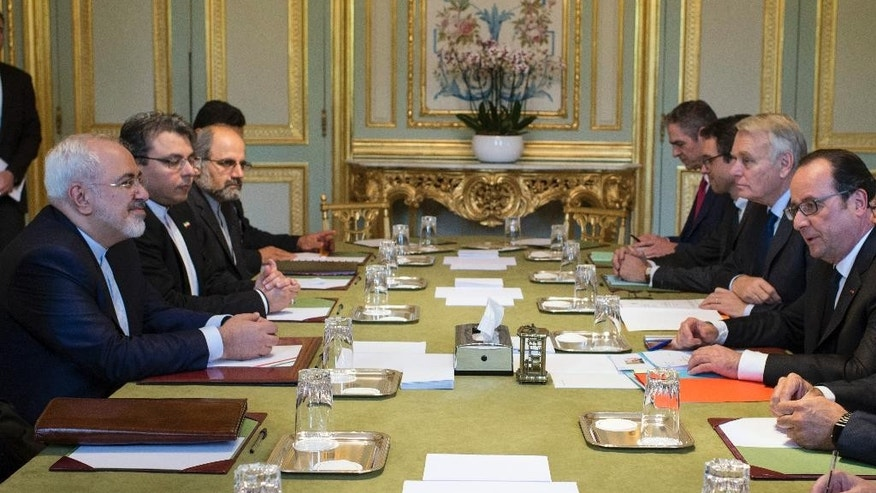 French President Francois Hollande, right, faces Iranian Foreign Minister Mohammad Javad Zarif during his meeting at the Elysee Palace in Paris, France, Thursday June 22, 2016. Iran's foreign minister is holding a string of meetings in Paris to seek benefits from a nuclear accord, hoping to maintain the momentum toward change before it runs out. (Jeremy Lempin, Pool via AP)