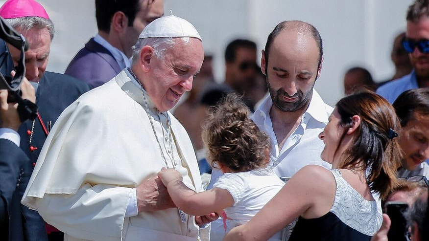 Pope Francis caresses a child at the end of his weekly general audience in St. Peter's Square at the Vatican, Wednesday, June 22, 2016. (AP Photo/Fabio Frustaci)