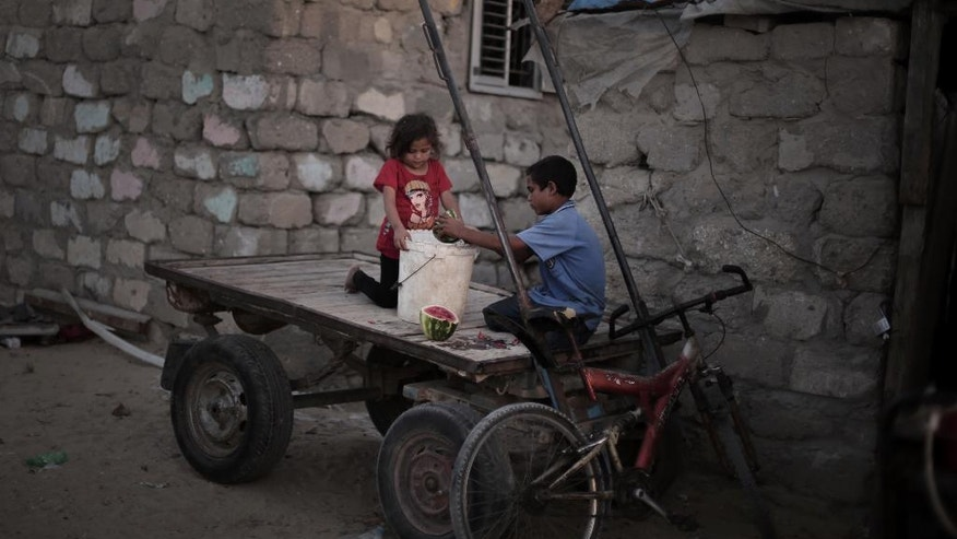 In this Monday, June 20, 2016 photo, Palestinian children prepare food for a horse as they sit on a cart next to their house in El-Zohor slum on the outskirts of Khan Younis refugee camp, southern Gaza Strip. The expansion of the el-Zohor slum, where barefoot children play in the rusty skeletons of discarded vehicles surrounded by mountains of garbage, is a sign of the times in Gaza, where poverty is growing and there is little hope for the future. While Gaza has always been poor, conditions for the 1.8 million people who live in the crowded seaside territory worsened since the Islamic militant group Hamas seized power in 2007. (AP Photo/ Khalil Hamra)