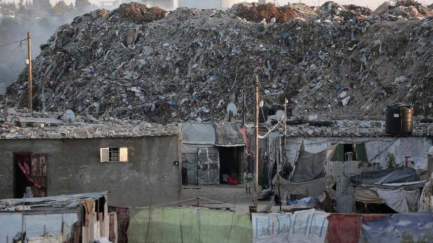 In this Monday, June 20, 2016 photo, piles of garbage surround el-Zohor slum, on the outskirts of Khan Younis refugee camp, southern Gaza Strip. The expansion of the slum, where barefoot children play in the rusty skeletons of discarded vehicles surrounded by mountains of garbage, is a sign of the times in Gaza, where poverty is growing and there is little hope for the future. While Gaza has always been poor, conditions for the 1.8 million people who live in the crowded seaside territory worsened since the Islamic militant group Hamas seized power in 2007. (AP Photo/ Khalil Hamra)
