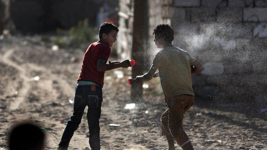 In this Monday, June 20, 2016 photo, Palestinian boys play with water toys in el-Zohor slum on the outskirts of Khan Younis refugee camp, southern Gaza Strip. The expansion of the el-Zohor slum, where barefoot children play in the rusty skeletons of discarded vehicles surrounded by mountains of garbage, is a sign of the times in Gaza, where poverty is growing and there is little hope for the future. While Gaza has always been poor, conditions for the 1.8 million people who live in the crowded seaside territory worsened since the Islamic militant group Hamas seized power in 2007. (AP Photo/ Khalil Hamra)