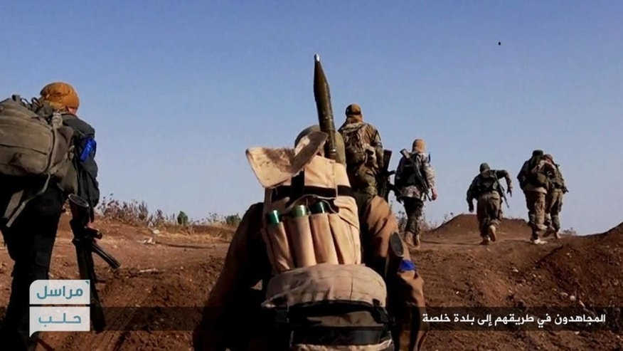 """FILE - This file image posted on the Twitter page of Syria's al-Qaida-linked Nusra Front on Tuesday, June 14, 2016, which is consistent with AP reporting, shows Nusra Front fighters moving forward to fight against Syrian troops and pro-government gunmen at the hilltop of Khalsa village, southern Aleppo, Syria. The Syrian government has suffered serious setbacks in its campaign to retake the Islamic State's de facto capital of Raqqa, even with Russia's support. Arabic, bottom right, reads, """"Jihadis on their way to Khalsa village."""" (Al-Nusra Front Twitter page via AP, File)"""