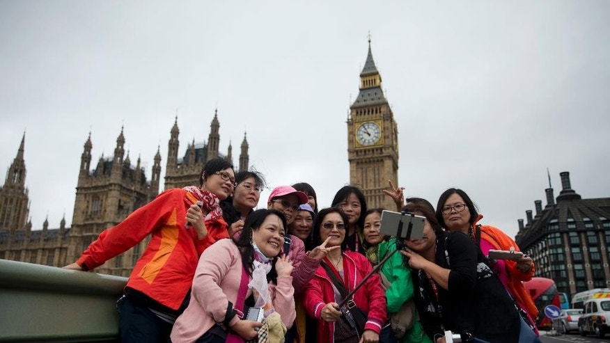 Tourists take a selfie backdropped by the Houses of Parliament in London, Wednesday, June 22, 2016. Britain votes whether to stay in the European Union in a referendum on Thursday. (AP Photo/Matt Dunham)