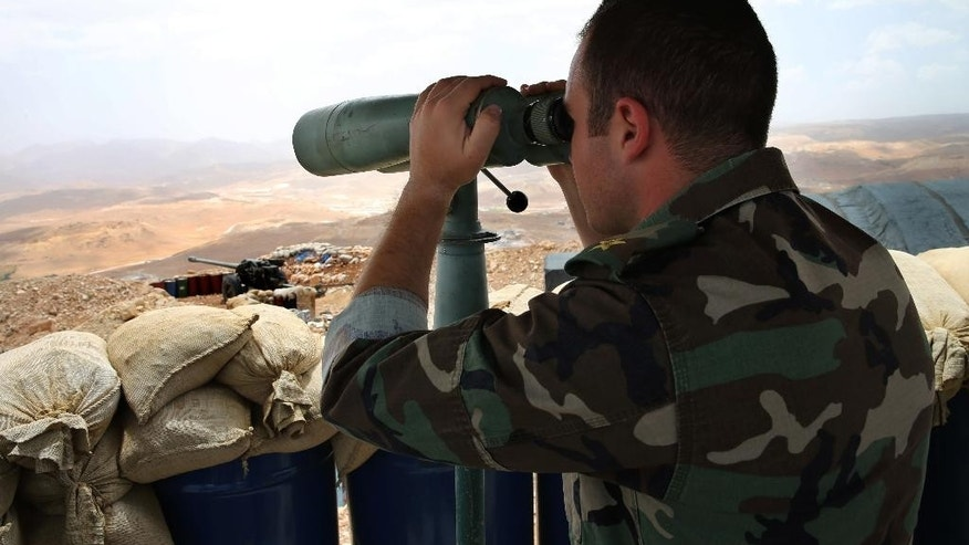 In this Sunday June 19, 2016 photo, a Lebanese army first lieutenant looks through binoculars toward areas controlled by the Islamic State group at the edge of the town of Arsal, on the Syrian border, in northeast Lebanon. The Lebanese army is fighting a war against the Islamic State and al-Qaida and has clawed significant territory back from the extremists. The fighting and shelling near the eastern border town of Arsal occur almost daily. Some 5,000 Lebanese soldiers are fighting against a dwindling number of militants. (AP Photo/Hussein Malla)