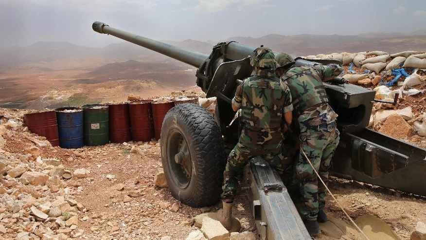 In this Sunday June 19, 2016 photo, Lebanese army soldiers work on a 130mm howitzer cannon, pointed to areas controlled by the Islamic State group at the edge of the town of Arsal, on the Syrian border, in northeast Lebanon. The Lebanese army is fighting a war against the Islamic State and al-Qaida and has clawed significant territory back from the extremists. The fighting and shelling near the eastern border town of Arsal occur almost daily. Some 5,000 Lebanese soldiers are fighting against a dwindling number of militants. (AP Photo/Hussein Malla)