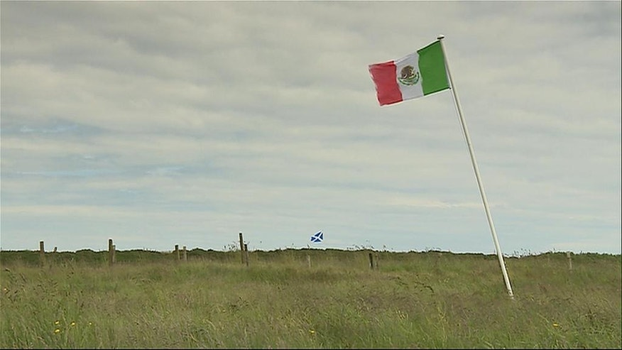 The Mexican flag, foreground, and the Scottish flag blow in the wind on land  near Turnberry golf course in Scotland  owned by David Milne one of  Donald Trump's long-standing opponents in Scotland on this image taken from video Wednesday June 22, 2016. Trump is scheduled to relaunch his Turnberry golf course and hotel in South Ayrshire  Scotlandon Friday following a  multi million revamp at the resort.(STV via AP) UNITED KINGDOM OUT TV OUT ONE TIME USE ONLY NO ARCHIVE NO SALES
