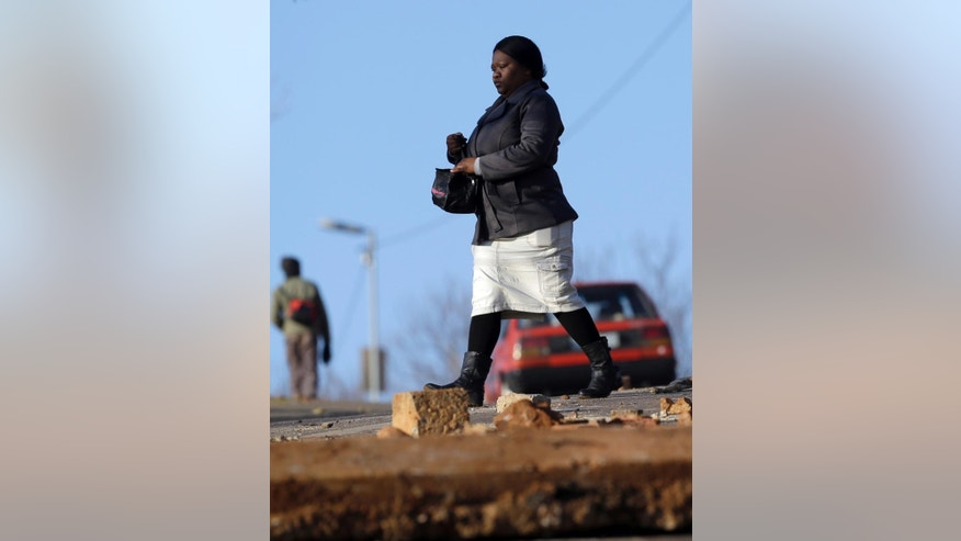 A woman a walks across a street littered with boulder and debris, after riots, in Atteridgeville, Pretoria, South Africa, Wednesday, June 22, 2016. Some residents in several poor areas of South Africa's capital, Pretoria, blocked roads, looted shops and burned vehicles Tuesday in riots attributed to discontent over the selection of the ruling party's mayoral candidate. (AP Photo/Themba Hadebe)