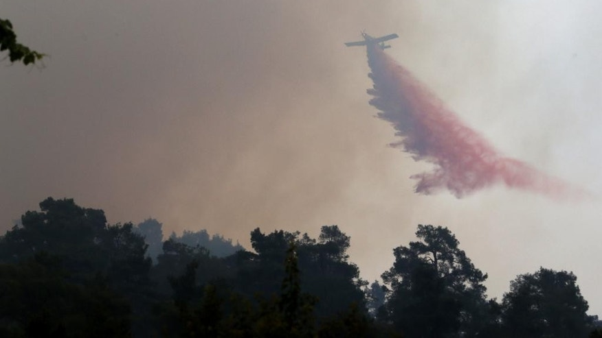 A firefighting aircraft drops fire retardant material in efforts to contain a huge forest fire that continues to rage out of control for a third day, in the mountainous areas southwest of Cyprus' capital Nicosia Tuesday, June 21, 2016. The fire has claimed the lives of two fire fighters. More planes from Italy and France are expected later Tuesday to join 16 other aircraft from Greece, Israel, Cyprus and British forces stationed on two military bases on the east Mediterranean island in battling the fire. (AP Photo/Philippos Christou )
