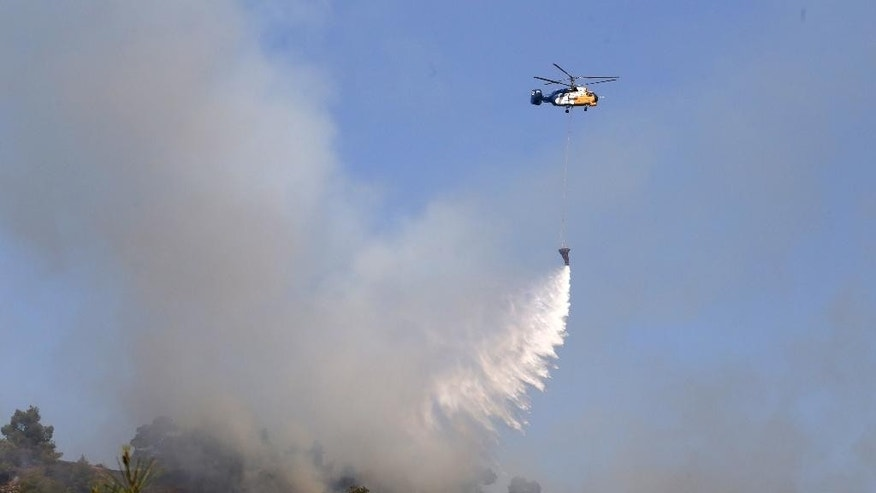 A helicopter drops water in efforts to contain a huge forest fire that continues to rage out of control for a third day in the mountainous areas southwest of Cyprus' capital Nicosia Tuesday, June 21, 2016. The fire has claimed the lives of two fire fighters. More planes from Italy and France are expected later Tuesday to join 16 other aircraft from Greece, Israel, Cyprus and British forces stationed on two military bases on the east Mediterranean island in battling the fire. (AP Photo/Philippos Christou )