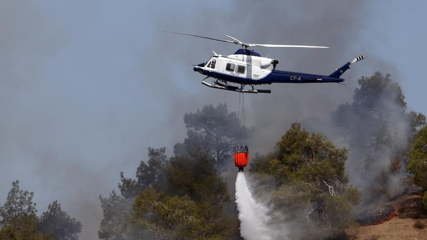 A police helicopter drops water in efforts to contain a huge forest fire that continues to rage out of control for a third day in the mountainous areas southwest of Cyprus' capital Nicosia Tuesday, June 21, 2016. The fire has claimed the lives of two fire fighters. More planes from Italy and France are expected later Tuesday to join 16 other aircraft from Greece, Israel, Cyprus and British forces stationed on two military bases on the east Mediterranean island in battling the fire. (AP Photo/Philippos Christou )