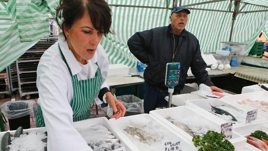 Fishmonger Dave Crosbie, right, and his wife Kim speak to the Associated Press at the market in Haverig's Romford street market in London, Wednesday, June 1, 2016. When Britain decides on Thursday June 23, 20916, whether to leave the European Union, London's voice may prove decisive. But for which side? Britain's capital, home to almost 9 million people, encompasses the most pro-EU place of the country, and the least. In the cosmopolitan City financial district, where almost half a million people from around the globe work in Europe's biggest financial center, pro-EU sentiment predominates. But just a few miles away, the borough of Havering, stronghold of working-class East Enders, topped a national survey of the most anti-EU places in Britain. (AP Photo/Frank Augstein)