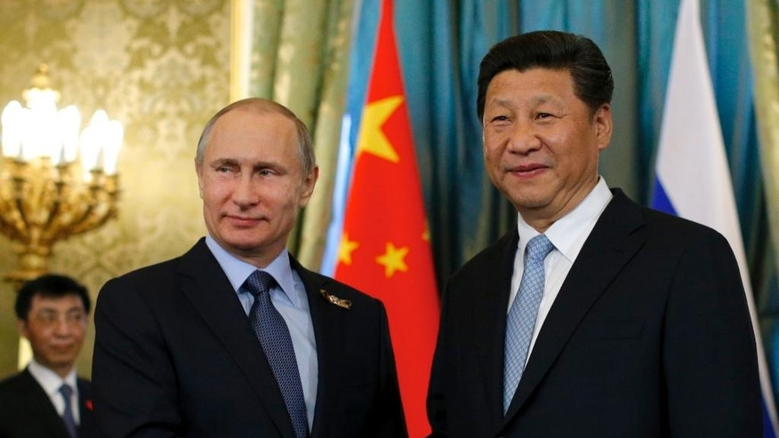 "FILE - In this Friday, May 8, 2015 file photo Russian President Vladimir Putin, left, shakes hands with his Chinese counterpart Xi Jinping during their meeting in the Kremlin in Moscow, Russia. With President Vladimir Putin heading to China this weekend, officials in both countries extoll a blossoming ""strategic partnership"" between the two former Communist rivals. (AP Photo/Alexander Zemlianichenko, pool, File)"