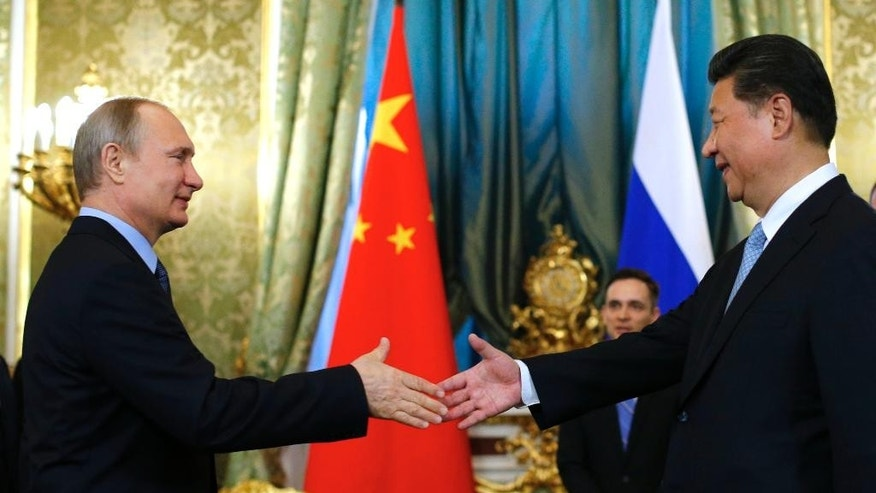 "FILE - In this Friday, May 8, 2015 file photo Russian President Vladimir Putin, left, welcomes his Chinese counterpart Xi Jinping during their meeting in the Kremlin in Moscow, Russia. With President Vladimir Putin heading to China this weekend, officials in both countries extoll a blossoming ""strategic partnership"" between the two former Communist rivals.  (AP Photo/Alexander Zemlianichenko, Pool, File)"