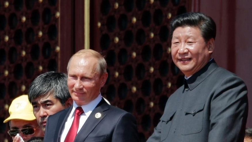 "FILE - In this Sept. 3, 2015 file photo, Chinese President Xi Jinping, right, Russian President Vladimir Putin, center, and South Korean President Park Guen-hye, seated left, observe a parade commemorating the 70th anniversary of Japan's World War II defeat, from Tiananmen Gate in Beijing. With President Vladimir Putin heading to China this weekend, officials in both countries extoll a blossoming ""strategic partnership"" between the two former Communist rivals. (AP Photo/Ng Han Guan, File)"