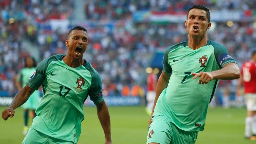 Portugal's Cristiano Ronaldo celebrates with teammate Nani, left, after scoring his side's second goal during the Euro 2016 Group F soccer match between Hungary and Portugal at the Grand Stade in Decines-­Charpieu, near Lyon, France, Wednesday, June 22, 2016. (AP Photo/Darko Bandic)