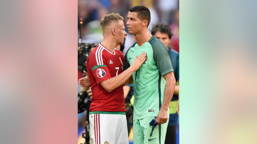 Balazs Dzsudzsak, left, of Hungary and Cristiano Ronaldo of Portugal embrace after end of the soccer Euro 2016 Group F third round match Hungary vs Portugal in Stade de Lyon in Lyon, France, Wednesday, June 22, 2016. The match ended in a 3-3 draw. (Tibor Illyes/MTI via AP)