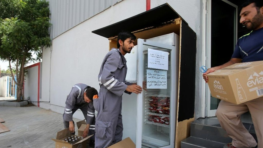 "In this Tuesday, June 21, 2016 photo, volunteers for ""Sharing Fridge"" campagin fill a fridge with food and water at the Al Quoz district in Dubai, United Arab Emirates. A campaign in the United Arab Emirates is stocking over 90 outdoor refrigerators with food and water for laborers during the Muslim holy fasting month of Ramadan. The ""Sharing Fridge"" group is run by volunteers across the country who restock each fridge up to 15 times a day. (AP Photo/Kamran Jebreili)"