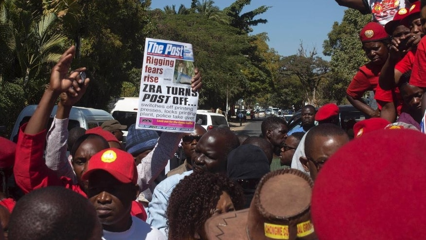 People protest over the closure of The Post newspaper in Lusaka, Zambia, Wednesday, June 22, 2016. Zambia's government has closed the country's largest independently owned newspaper over unpaid taxes, but the paper's owner says the move is meant to shut him up before elections in August. (AP Photo/Moses Mwape)