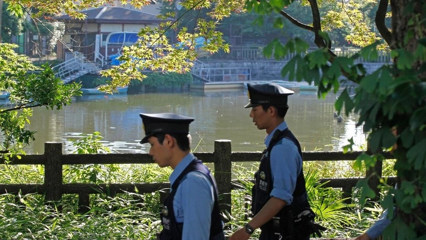 Police officers walk around a pond after a body part of a person was found floating in the water at Himonya Park in Tokyo's quiet residential area Thursday, June 23, 2016.  Japanese police are attempting to determine the identity and cause of death of the person. (AP Photo/Shuji Kajiyama)