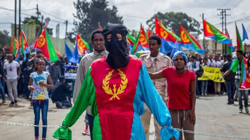 A woman dressed in the colors of the Eritrean flag stands symbolically chained, at a demonstration by Eritrean refugees and dissidents outside the headquarters of the African Union in Addis Ababa, Ethiopia, Thursday, June 23, 2016. Hundreds of Eritrean refugees and dissidents in Ethiopia have demonstrated against alleged human rights abuses committed by Eritrea's government, and supporting a new U.N. report that accuses it of crimes against humanity over the last 25 years. (AP Photo/Mulugeta Ayene)